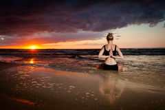 Meditation yoga on a beach. Summer yoga session on a beautiful golden beach - polish Grzybowo village, near to Kolobrzeg. Meditation - lotus pose - padma asana Stock Photography