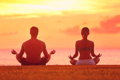 Meditation yoga couple meditating at beach sunset. Meditation yoga couple meditating at serene beach sunset. Girl and men relaxing in lotus pose in calm zen Royalty Free Stock Photo
