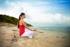 Meditation yoga woman on beach meditating by ocean sea sitting i Stock Photography