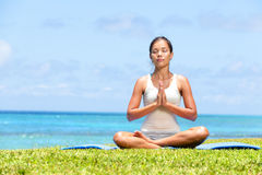 Meditation yoga woman on beach meditating by ocean. Sea sitting in lotus position with back turned serene and happy. Asian girl sitting relaxing enjoying summer Stock Images