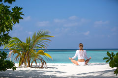 Meditation Yoga woman meditating at serene tropical beach. Girl relaxing in lotus pose in calm zen moment at ocean water Stock Images