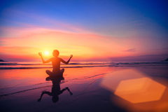 meditation Yogafrau, die auf Seeküste am Sonnenuntergang sitzt Lizenzfreie Stockfotos