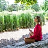 meditationen för den blonda flickan för 20-tal parkerar den praktiserande i en stad Royaltyfri Foto