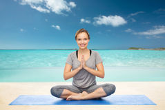 Meditationen för kvinnadanandeyoga i lotusblomma poserar på mattt Royaltyfri Fotografi