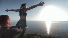 Meditationen på bakgrund av havet, mannen och kvinnan som gör yogaövningar med härligt, poserar på berget under solnedgång stock video