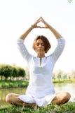 meditationen poserar kvinnan Händerna är ställen ovanför huvudet Arkivfoto