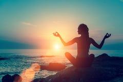 Meditationflicka på havet under solnedgång Arkivfoto