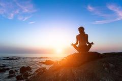 Meditationsfrau auf dem Ozean während des erstaunlichen Sonnenuntergangs stockfotografie