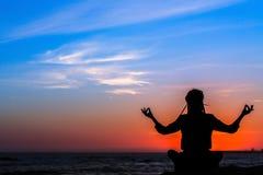 Meditationsfrauen-Yogaschattenbild, Ozean während des überraschenden Sonnenuntergangs relax lizenzfreie stockfotos