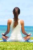 Meditationsyogafrau auf Strand meditierend durch Ozean Stockfoto