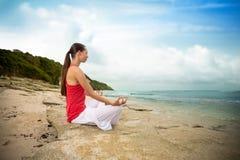 Meditationyogakvinna på stranden som mediterar vid havhavssammanträde I Arkivbild