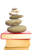 Meditative books. Pile of stones on some books for your concepts involving knowledge about nature, purity, peace, religion and others - isolated on white stock photography