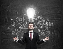Meditative businessman is looking for new business ideas. Drawn business icons on the black chalk board and a light bulb as Royalty Free Stock Photos