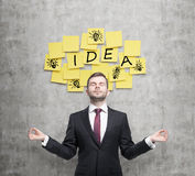 Meditative businessman is looking for new business ideas. Yellow stickers with the word ' idea' and sketches of ' light bulb Royalty Free Stock Photography