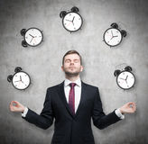 Meditative businessman is pondering about time management. The person in formal suit is surrounded by alarm clocks. There is a con. Crete wall in the room Royalty Free Stock Photography