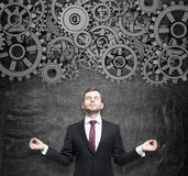 Meditative businessman is thinking about the project optimisation. Gears as a concept of thought working process. Royalty Free Stock Images