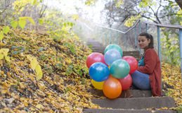 Meditative girl with her balloons. In autumn royalty free stock images