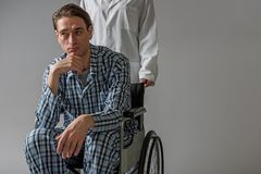 Meditative invalid transported in chair by nurse. Portrait of young paralyzed man with pensive expression carrying in wheelchair by medical worker. Copy space in Stock Photo