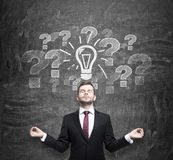Meditative man is looking for the best business ideas to start a new business. Question marks and a light bulb are on the Stock Image
