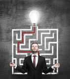 Meditative man and solved labyrinth with a light bulb on the black chalk board. Stock Photos
