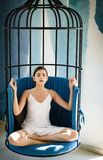 Meditative and tranquil. Cute woman concentrate and meditate in chair. Woman relax in lotus position at home. Pretty royalty free stock images