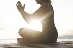 Meditative woman prays in front of the sea Royalty Free Stock Photos