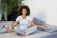 Meditazione di pratica di yoga della giovane donna sul suo letto immagini stock libere da diritti