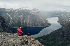 Meditazione di rilassamento dell'uomo del viaggiatore con le montagne serene di vista e Fotografia Stock