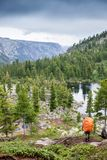 Meditazione di rilassamento dell'uomo del viaggiatore con lo stile di vita di viaggio del paesaggio delle montagne e del lago di  Fotografia Stock Libera da Diritti