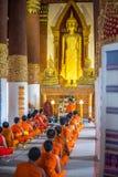 Meditazione di vipassana del monaco dei principianti alla parte anteriore della statua di Buddha Fotografie Stock Libere da Diritti