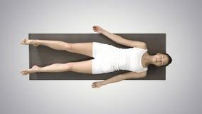 Meditazione di yoga che mette su una stuoia con gli occhi chiusi sul fondo di pendenza video d archivio
