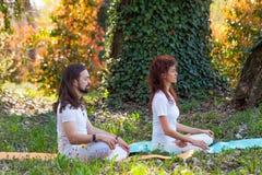 Meditazione di yoga di pratica della donna e del giovane nell'ente completo di vista laterale della natura sparato in legno immagini stock