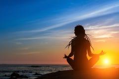 Meditazione e stile di vita sano sull'oceano durante il tramonto stupefacente fotografia stock