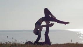 Meditazione su aria aperta, sulla donna e sull'uomo facenti yoga di paia sulla montagna su fondo del mare e del tramonto video d archivio