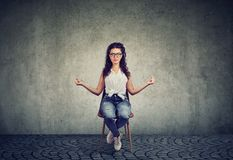 Meditera kvinnan på stol med stängda ögon fotografering för bildbyråer