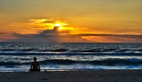 Meditera på stranden på soluppgång arkivfoton