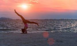 Mediterar att öva för livsstil för ung kvinna för kontur som är livsviktigt, och praktiserande yoga på stranden på solnedgången royaltyfri foto