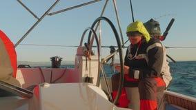 MEDITERRÂNEO - CERCA DO NOVEMBRO DE 2017: O marinheiro no dever olha o smartphone que senta-se na roda do boi do iate controlada  video estoque
