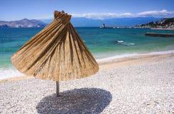 Mediterranean beach. Single umbrella on mediterranean beach Stock Photos