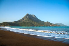 Mediterranean beach with a mountain in the background. The cove / bay of Adrasan at the Turquoise Coast near Antalya. Blue sea, blue sky and a dark brown sandy Royalty Free Stock Images