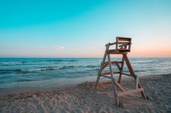 Beach with wooden lifeguard chair in sunset time. Mediterranean beach with wooden lifeguard chair in sunset time, Oliva Beach in Valencia province, Spain. Teal stock image