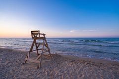 Beach with wooden lifeguard chair in sunset time. Mediterranean beach with wooden lifeguard chair in sunset time, Oliva Beach in Valencia province, Spain royalty free stock images