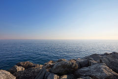 Mediterranean blue, calm sea with horizon and rocks, Italy. Mediterranean blue, calm sea with horizon and rocks, clear sky in Italy Royalty Free Stock Image