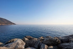 Mediterranean blue, calm sea with rocks and coast, Italy. Mediterranean blue, calm sea with rocks and coast, clear sky in Italy Royalty Free Stock Photo