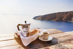 Mediterranean breakfast, cup of coffee and fresh bread on a table with beautiful sea view at the background. Cup of coffee and fresh bread on a table with Royalty Free Stock Image