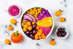 Mediterranean Buddha bowl with roasted pumpkin, olives, turmeric chickpeas, beet hummus, shredded red cabbage, tomatoes. Mediterranean Buddha bowl with roasted Stock Images