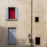 Mediterranean Clayed Yellow Warm Facade with Pastel Colored Wooden Shutters and Red Curtain, France Stock Image