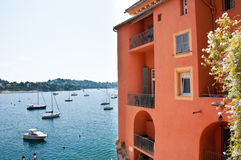 Mediterranean coast. Bright red Mediterranean building in the south of France set against a backdrop of blue sea and boats in a harbour Stock Image