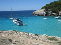 Mediterranean coast of turquoise waters. With boats anchored in the vicinity of the beach. Vacations on board stock images