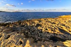 Mediterranean coastline at sunset, Malta. Limestone rocks and mediterranean seacoast at sunset, Malta, Bugibba resort Royalty Free Stock Image